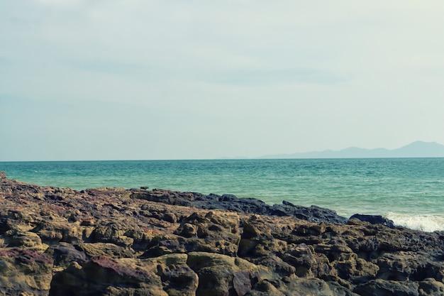 Kamienna plaża i morze z niebieskie niebo natury tapety tłem