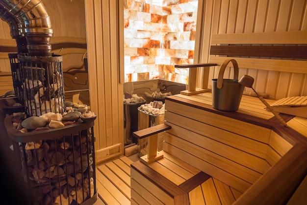 Kamienna ściana sauny z oświetleniem od wewnątrz klasyczne akcesoria do wanny chochla i wiadro