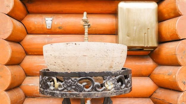 Kamienna umywalka na metalowym kutym stojaku w domu z bali. wnętrze domu wykonane z drewna.