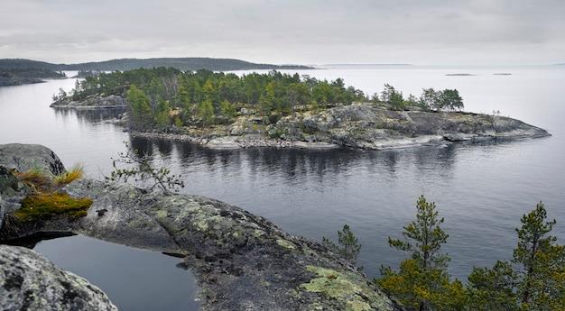 Kamienna wyspa, porośnięta lasem w środku północnego jeziora ładoga w regionie karelia w rosji
