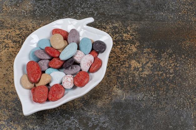 Kamienne cukierki owalne na talerzu w kształcie liścia.