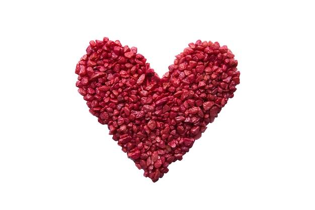 Kamienne czerwone serce wyłożone małymi ozdobnymi kamieniami na białym tle