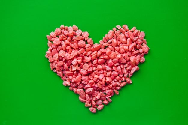 Kamienne czerwone serce wyłożone małymi ozdobnymi kamieniami na zielonym tle