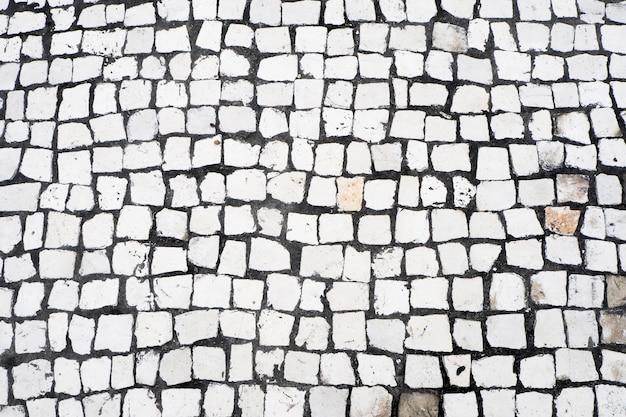Kamienne kamienie brukowe. brukowiec w stylu portugalskim makau. motyw płytki w largo do senado - senat, portugalski chodnik senado square, makau