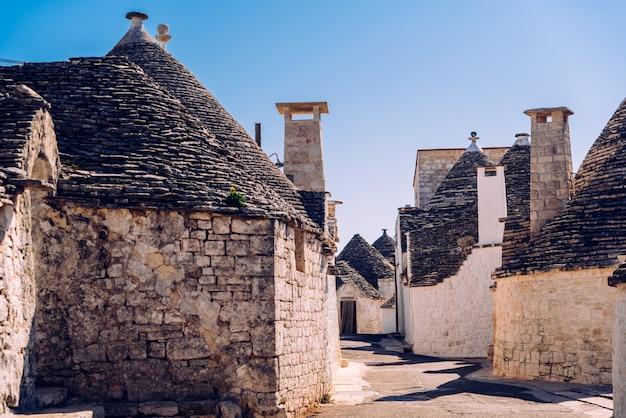 Kamienne płytki pokrywają dachy trulli w alberobello, włoskim mieście, które warto odwiedzić podczas podróży do włoch.