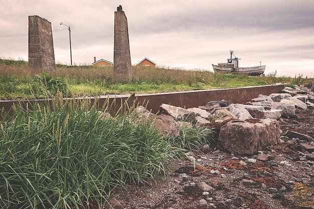 Kamienne ruiny i stara łódź na brzegu, norwegia