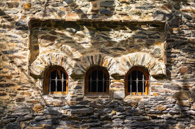 Kamienne teksturowane łuki okienne z cieniami drzew