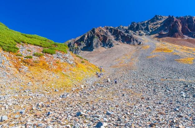 Kamienne zbocze wulkanu z pieszymi turystami.