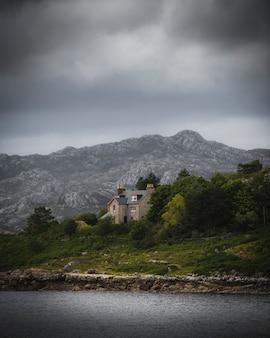 Kamienny dom nad jeziorem w pochmurny dzień