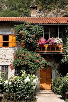 Kamienny dom z dachem krytym dachówką z kwitnącymi krzewami w pobliżu. tło