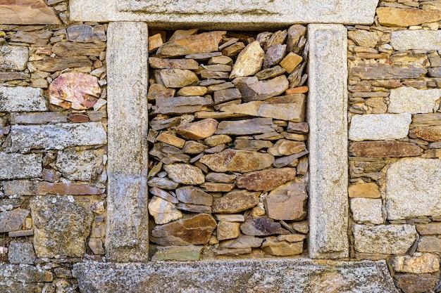 Kamienny dom z oknem zabitym starymi kamieniami.
