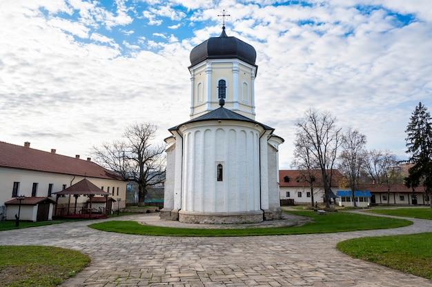 Kamienny kościół na wewnętrznym dziedzińcu klasztoru capriana. nagie drzewa, zielony trawnik i budynki. dobra pogoda w mołdawii