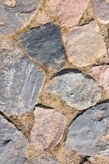 Kamienny mur, droga, tekstura kamienia naturalnego. tło.