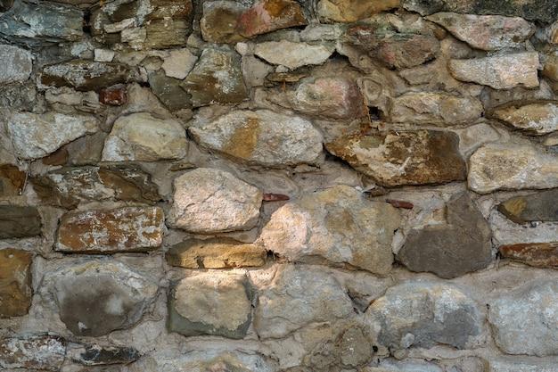 Kamienny mur, stary kruszący się kamienny mur z kamienia i piaskowca, abstrakcyjne tło natury
