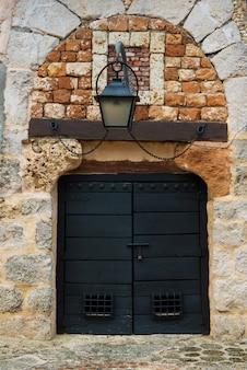 Kamienny mur z czarnymi drzwiami, stare tło.