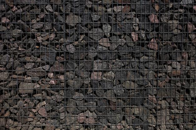 Kamienny mur z metalową siatką jako tło. tekstura skały