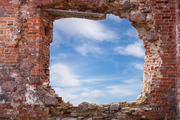 Kamienny mur z okrągłym otworem, z którego widać niebo z chmurami. zdjęcie wysokiej jakości