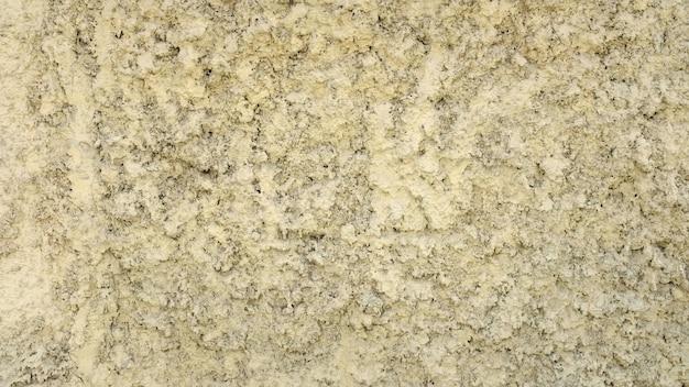 Kamienny mur z żółtym tynkiem. szorstka tekstura. zdjęcie wysokiej jakości