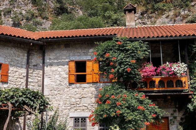Kamienny stary budynek z dachem krytym dachówką w europie z kwitnącymi krzewami latem