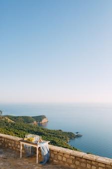 Kamienny stół z niebieską peleryną, kieliszkami do szampana i winogronami z widokiem na zielony las i morze