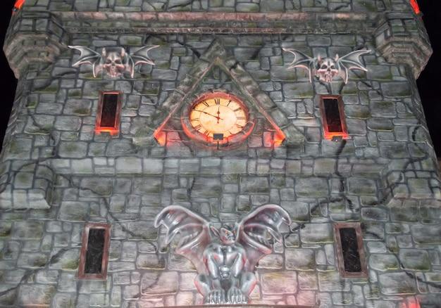 Kamienny zamek halloween ze świecącym zegarem i gargulcami. zbliżenie, widok z dołu. instalacja zamku grozy.