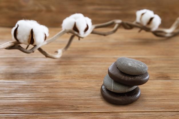 Kamienny zestaw do masażu z bawełnianą rośliną kwiatów i stosem kamieni na starej drewnianej powierzchni. naturalne tło.
