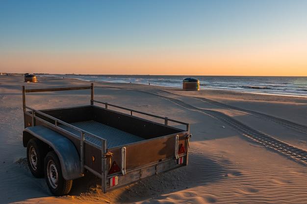 Kamper lub przyczepa na piaszczystej plaży w pięknym zachodzie słońca z spokojnym morzem w