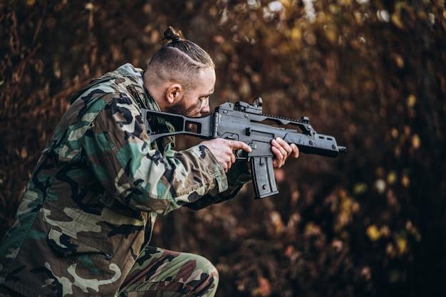 Kamuflaż żołnierz z karabinem i pomalowaną twarzą, grając w airsoft na świeżym powietrzu w lesie