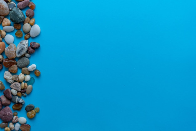 Kamyczki morskie płasko świeckich kompozycji na niebieskim tle. miejsce na tekst