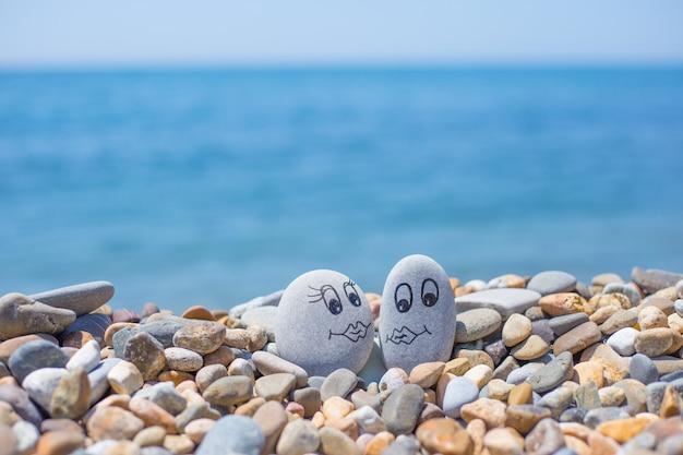 Kamyki z wymalowanymi twarzami na piasku. kochająca para. koncepcja podróży.