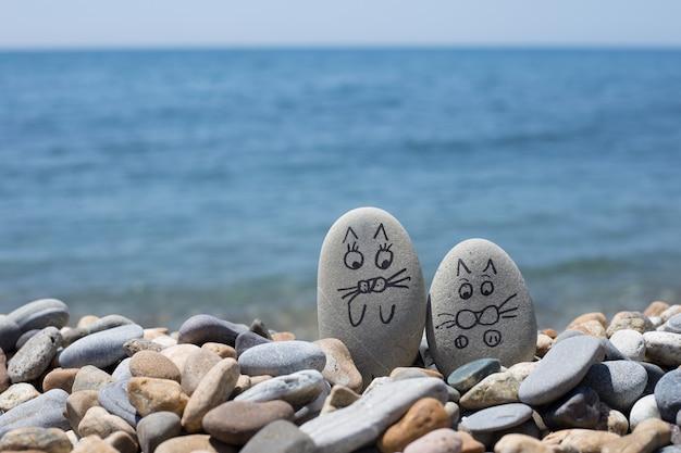 Kamyki z wymalowanymi twarzami na piasku. kochająca para.