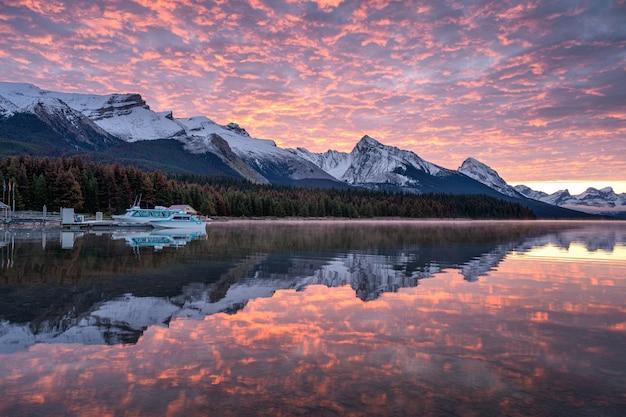 Kanadyjskie góry skaliste z komercyjnym dokiem i kolorowymi chmurami altocumulus odbicia na jeziorze maligne