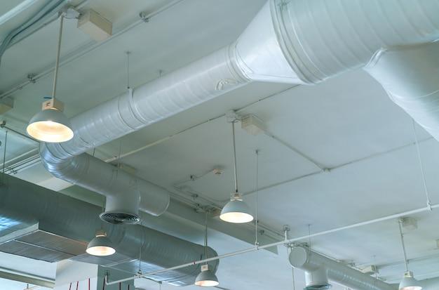 Kanał powietrzny, rura klimatyzatora, rura okablowania i instalacja tryskaczowa. system przepływu powietrza i wentylacji. wnętrze budynku. lampa sufitowa z otwartym światłem.