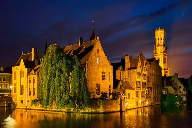 Kanał rozenhoedkaai z dzwonnicą i starymi domami wzdłuż kanału z drzewami w nocy.