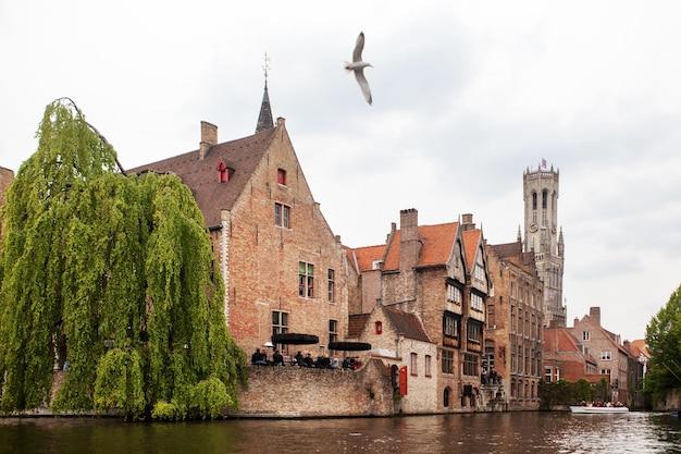 Kanał w brugii ze słynną wieżą belfry na powierzchni. belgia