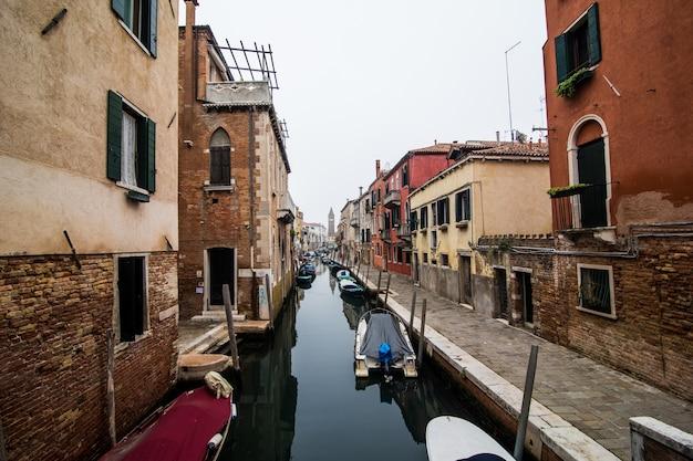 Kanał z gondolami w wenecji, włochy. architektura i zabytki wenecji. wenecka pocztówka z weneckimi gondolami.