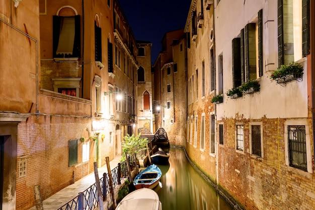 Kanał z łodziami i małym mostem w wenecji w nocy, włochy,