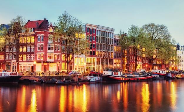 Kanałowe domy amsterdamu o zmierzchu z żywymi odbiciami