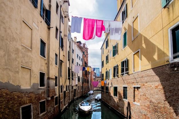 Kanały wenecji miejscowi mieszkańcy suszą ubrania nad kanałem między domami włochy