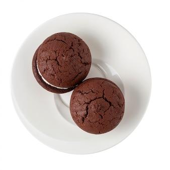Kanapek czekoladowi ciastka i śmietanka na białym talerzu odizolowywającym na bielu