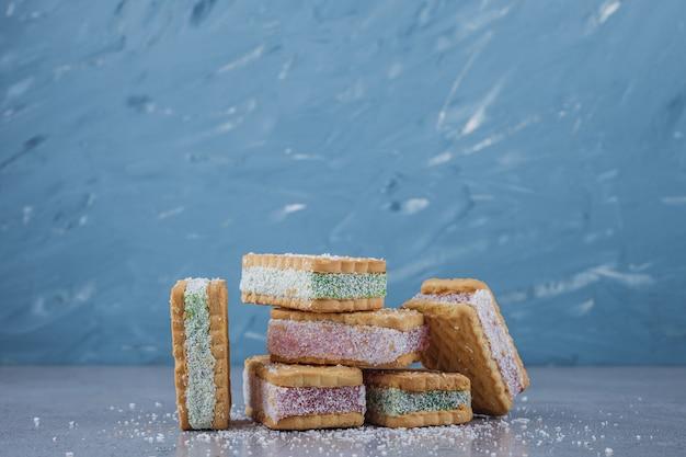 Kanapka biscuit wypełniona kolorową marmoladą na kamiennym tle.