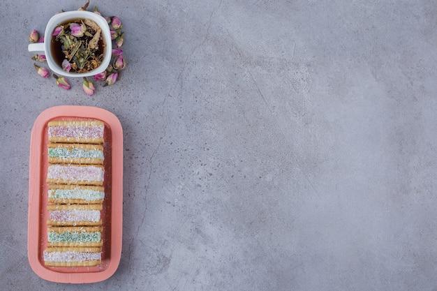 Kanapka biscuit wypełniona kolorową marmoladą na różowym talerzu i filiżanką herbaty.