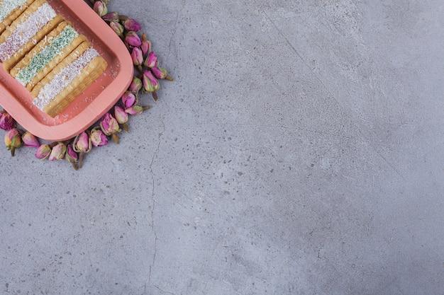 Kanapka biscuit wypełniona kolorową marmoladą na różowym talerzu.