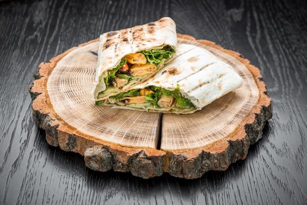 Kanapka bułka z paluszkami rybnymi, serem i warzywami zbliżenie na stole