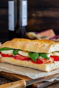 Kanapka caprese z pomidorami, mozzarellą, bazylią i boczkiem. zdrowe odżywianie. kuchnia włoska.
