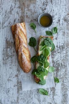 Kanapka ciabatta z pesto, ziołami, szynką parmeńską, salami, kiełbasą, mozzarellą i szpinakiem na szarym drewnie, widok z góry