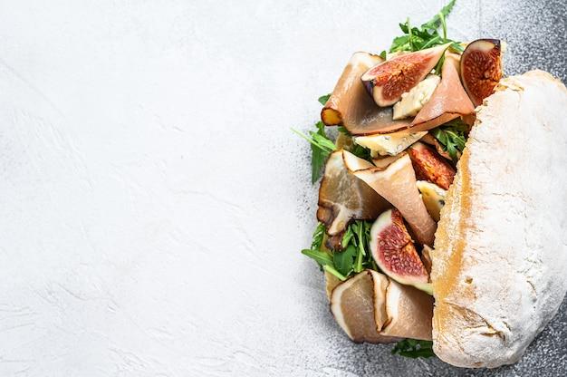 Kanapka ciabatta z rukolą, figą, prosciutto i serem pleśniowym. szare tło. widok z góry.