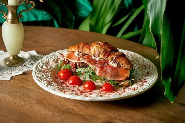 Kanapka croissant z jamonem, mozzarellą, rukolą, suszonymi pomidorami na drewnianym tle