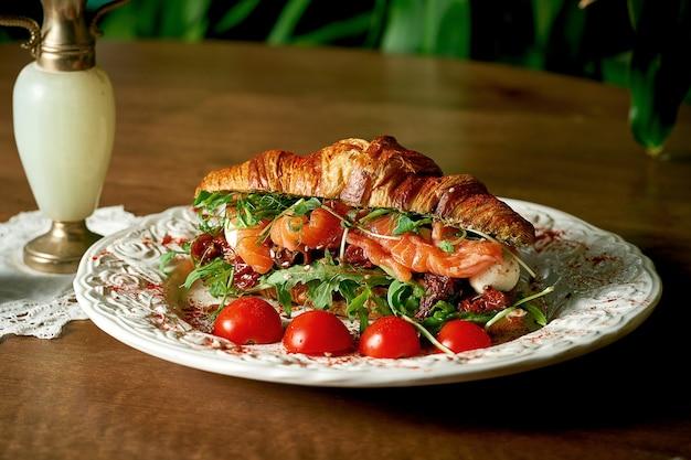 Kanapka croissant z łososiem, mozzarellą, rukolą, suszonymi pomidorami na drewnianym tle