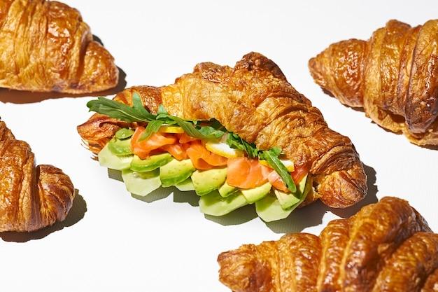 Kanapka croissant z łososiem, rukolą i awokado. ostre światło. białe tło